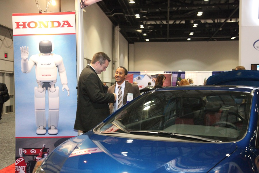 Show attendees exchange business cards at the Honda booth at the Business Opportunity Fair.